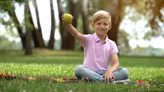 Menino mostrando maçã