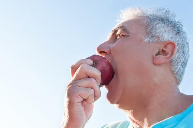 Homem comendo maçã