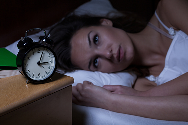 Mulher acordada olhando pro relógio